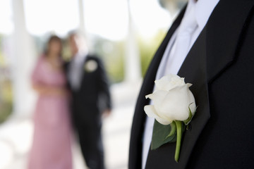 Groom wearing formal suit and buttonhole, couple looking on in background, focus on groom in foreground
