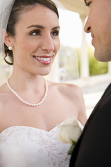 Bride and groom standing face to face at wedding, smiling, close-up, side view