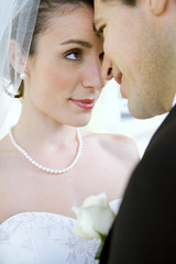 Affectionate bride and groom standing face to face at wedding, smiling, close-up, side view