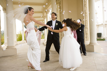 Bride and groom dancing with bridesmaid (8-10) in circle at wedding, couple throwing confetti, smiling