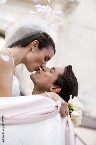 Bride and groom embracing and kissing outside church, profile, low angle view (tilt)