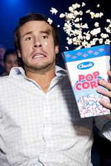 Man reacting to a film at the cinema, popcorn flying