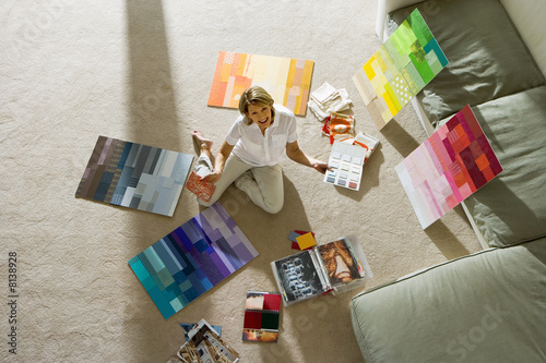 Mature woman sitting on floor at home, looking at colour charts, smiling, portrait, overhead view