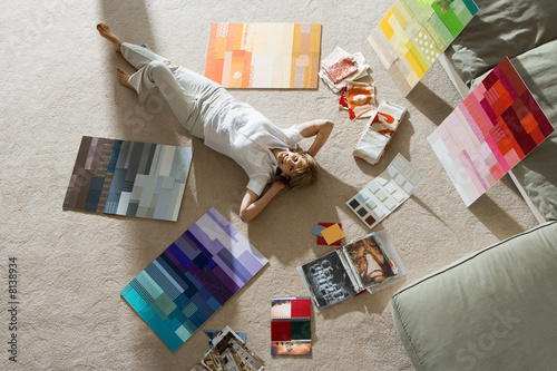 Senior man lying on floor at home, looking at colour charts, hands behind head, smiling, portrait, overhead view