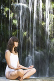 A woman meditating by a waterfall
