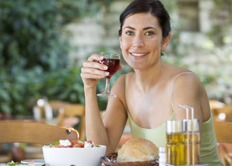 A woman drinking a glass of wine with a meal