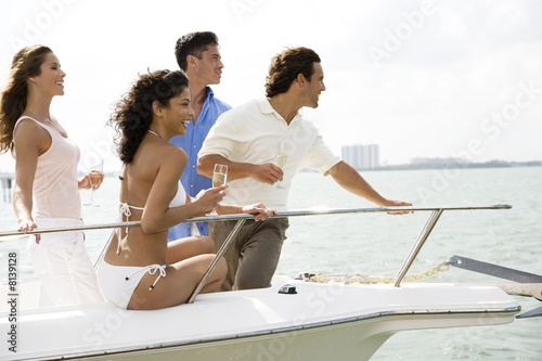 Two couples having drinks on board a luxury yacht
