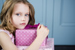 Young girl holding birthday presents looking unhappy