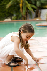 little Hispanic girl playing by the pool