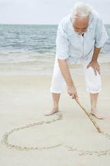 Portrait of a senior man drawing a heart shape in the sand