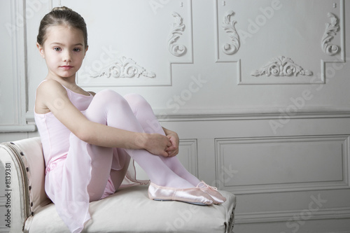 Young girl in a tutu and ballet shoes sitting on a chair