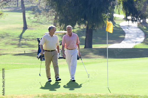 Two mature men playing golf, walking side by side on putting green, holding golf clubs, smiling