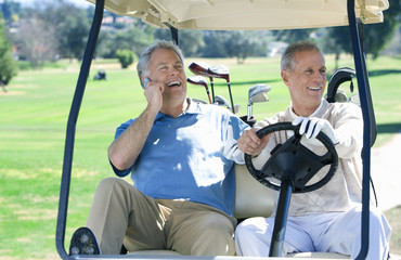 Two mature men sitting in golf buggy on golf course, one man driving, other man using mobile phone, smiling, front view