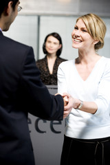 Businessman being greeted at office reception
