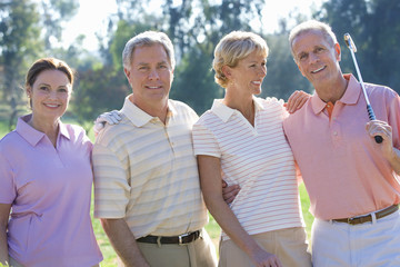 Two mature couples standing side by side on golf course, playing golf, smiling, close-up, front view, portrait