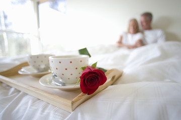 Mature couple sitting upright in bed, focus on breakfast tray with two coffee cups and single red rose in foreground