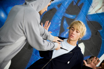 Confrontation between two young men in front of a graffiti covered wall