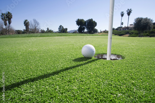 Golf ball at edge of hole on putting green, close-up (surface level)