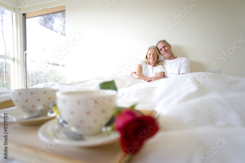 Breakfast tray with two coffee cups and single red rose on bed, focus on mature couple sitting upright in bed in background