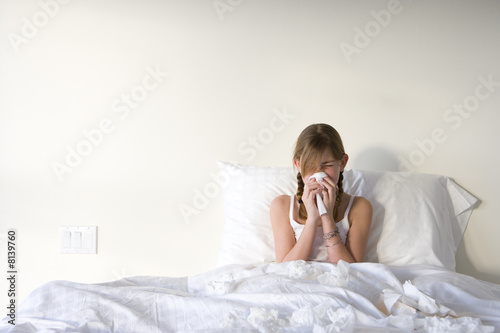 Girl (11-13) sitting upright in bed, blowing nose with handkerchief, front view