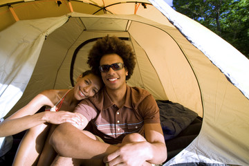 Young couple sitting in dome tent entrance on camping trip, woman leaning on man's shoulder, smiling, front view, portrait