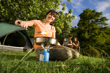 Friends sitting near tent in woodland clearing, focus on young woman cooking food on gas camping stove in foreground, smiling, portrait (tilt, surface level)