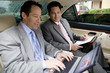 Two businessmen sitting in backseat of car, one man using laptop, other man holding folder, looking on