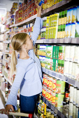 Young girl reaching up to get something off of a supermarket shelf