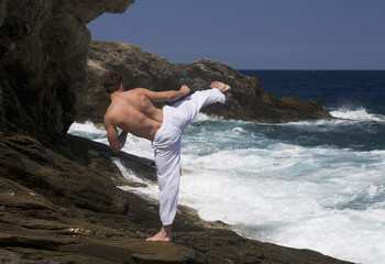 A man practicing Tai Chi by the sea