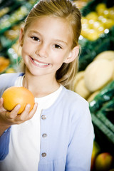 Portrait of a young girl holding a grapefruit in a supermarket