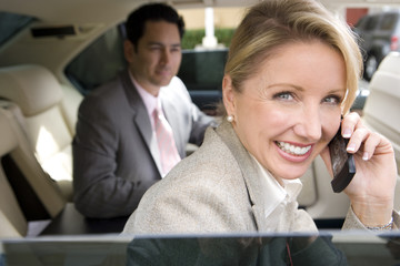 Businessman and woman sitting in backseat of car, focus on blonde woman using mobile phone in foreground, smiling, close-up, side view, portrait, view through open window