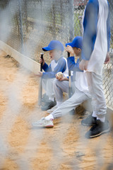 Little league baseball team seen through wire fence