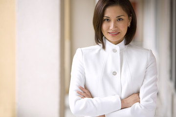 Businesswoman, with brown bobbed hair, wearing white business suit, arms folded, smiling, front view, portrait