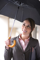 Businesswoman standing under black umbrella in rain, smiling, front view