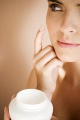 Woman applying moisturising cream to her face