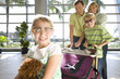 Family standing with luggage trolley in airport, girl (7-9) sitting on suitcase with soft toy in foreground, wearing sunglasses, smiling, portrait