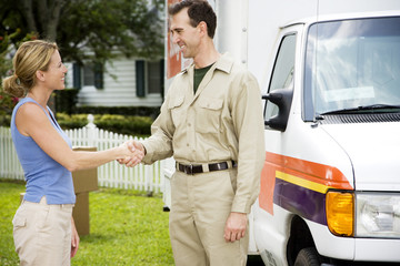 Woman shaking hands with removal man beside his van