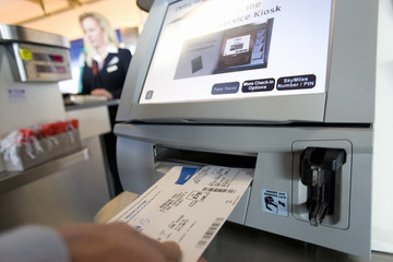 Traveller placing airline ticket into automatic check-in machine in airport, close-up, mid-section, rear view (differential focus)