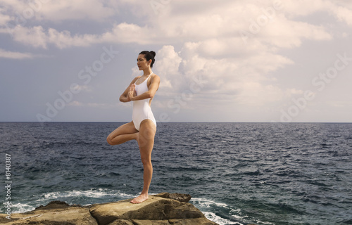 A woman meditating by the sea