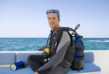 A man sitting on a boat preparing to go scuba diving