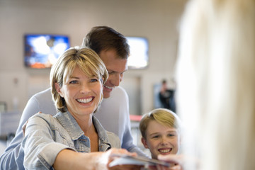 Family standing at airport check-in desk, woman handing passports to check-in attendant, smiling (differential focus)