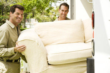 Removal men with sofa beside their van