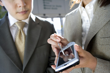 Businessman and woman standing in airport, looking at businesswoman's personal electronic organiser, close-up, mid-section