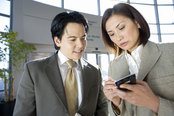 Businessman and woman standing in airport, looking at businesswoman's personal electronic organiser