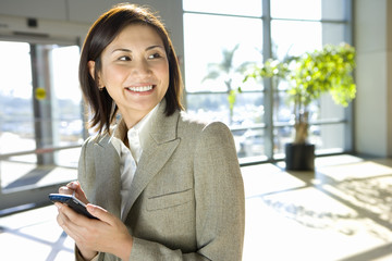 Businesswoman standing in airport, using personal electronic organiser, smiling