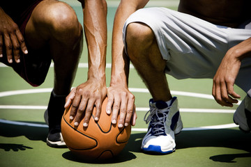 Two  African American kneeling side by side on an urban basketball court, close up