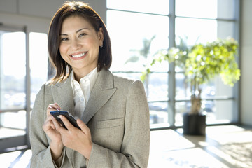 Businesswoman standing in airport, using personal electronic organiser, smiling, portrait