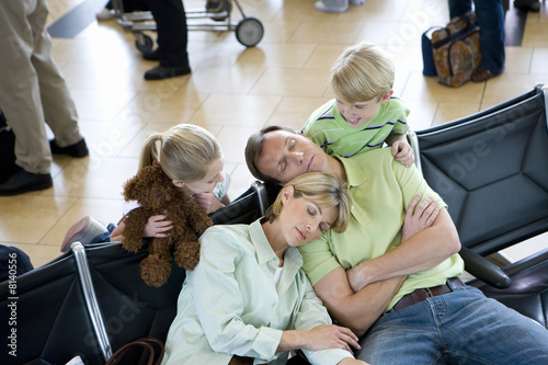 Family waiting in airport departure lounge, boy (8-10) and girl (7-9) watching parents sleeping, smiling, elevated view