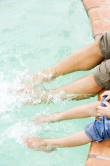 cropped image man and boy's feet splashing in swimming pool