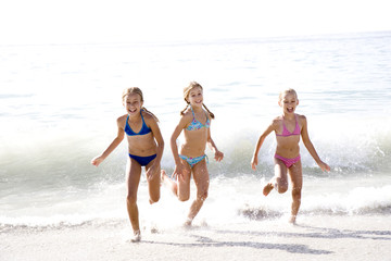 Three young girls running out of the sea